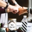 """five hands doing a fistbump over a table with some items on top of it, including a jar that says """"Go for it!"""" 