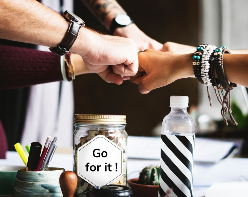"five hands doing a fistbump over a table with some items on top of it, including a jar that says ""Go for it!"" 
