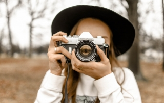 A woman holding a camera | image source: Pexels.com