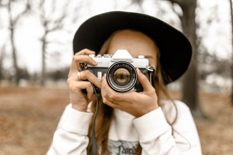 A woman holding a camera | image source: Pexels.com