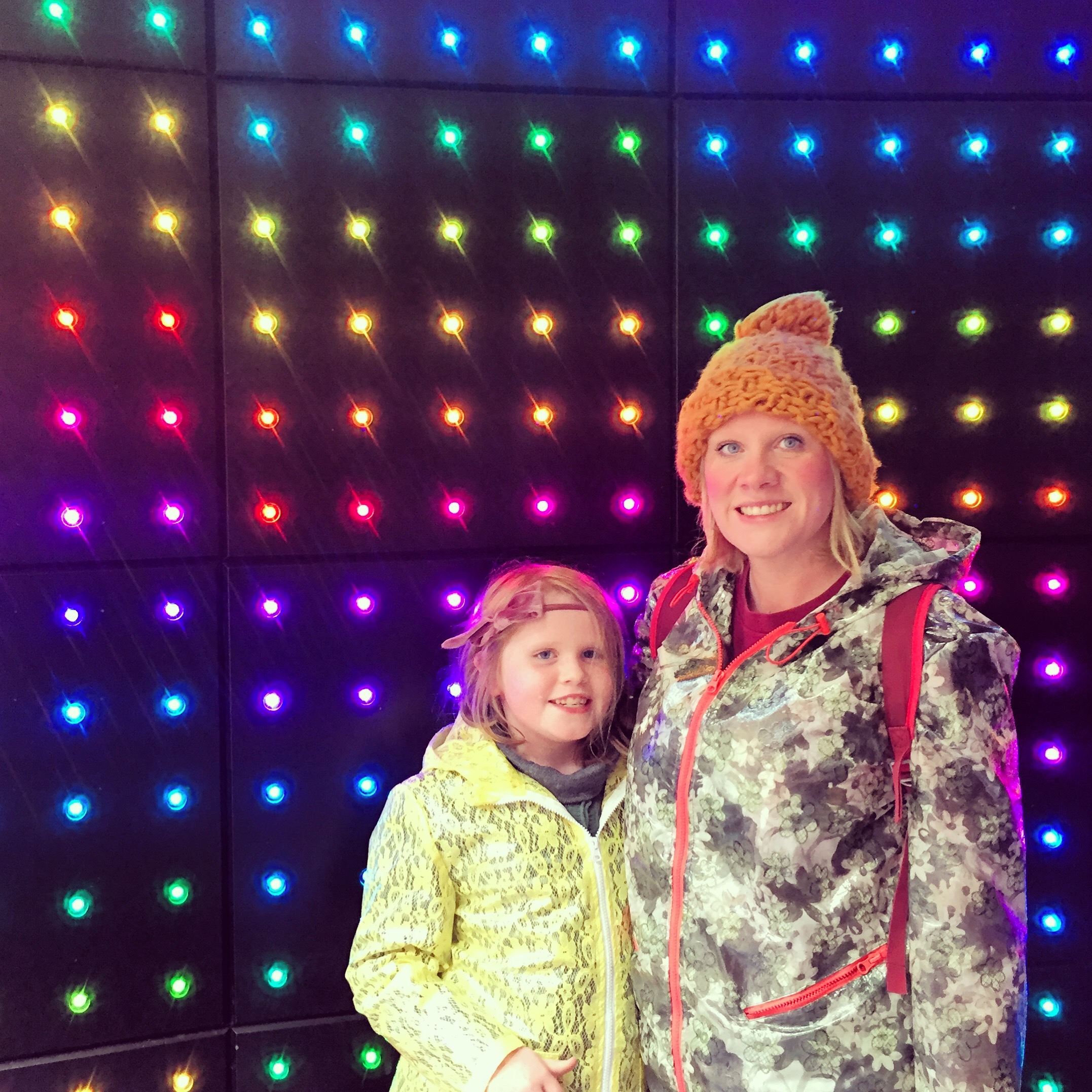 Image is a photograph of Amrick and her daughter wearing coats, stood in front of an LED wall of rainbow-coloured lights