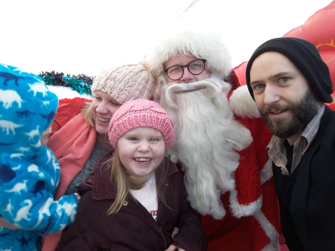 Image is a photograph of Amrick Ainley with her family, smiling for a group photograph with Father Christmas