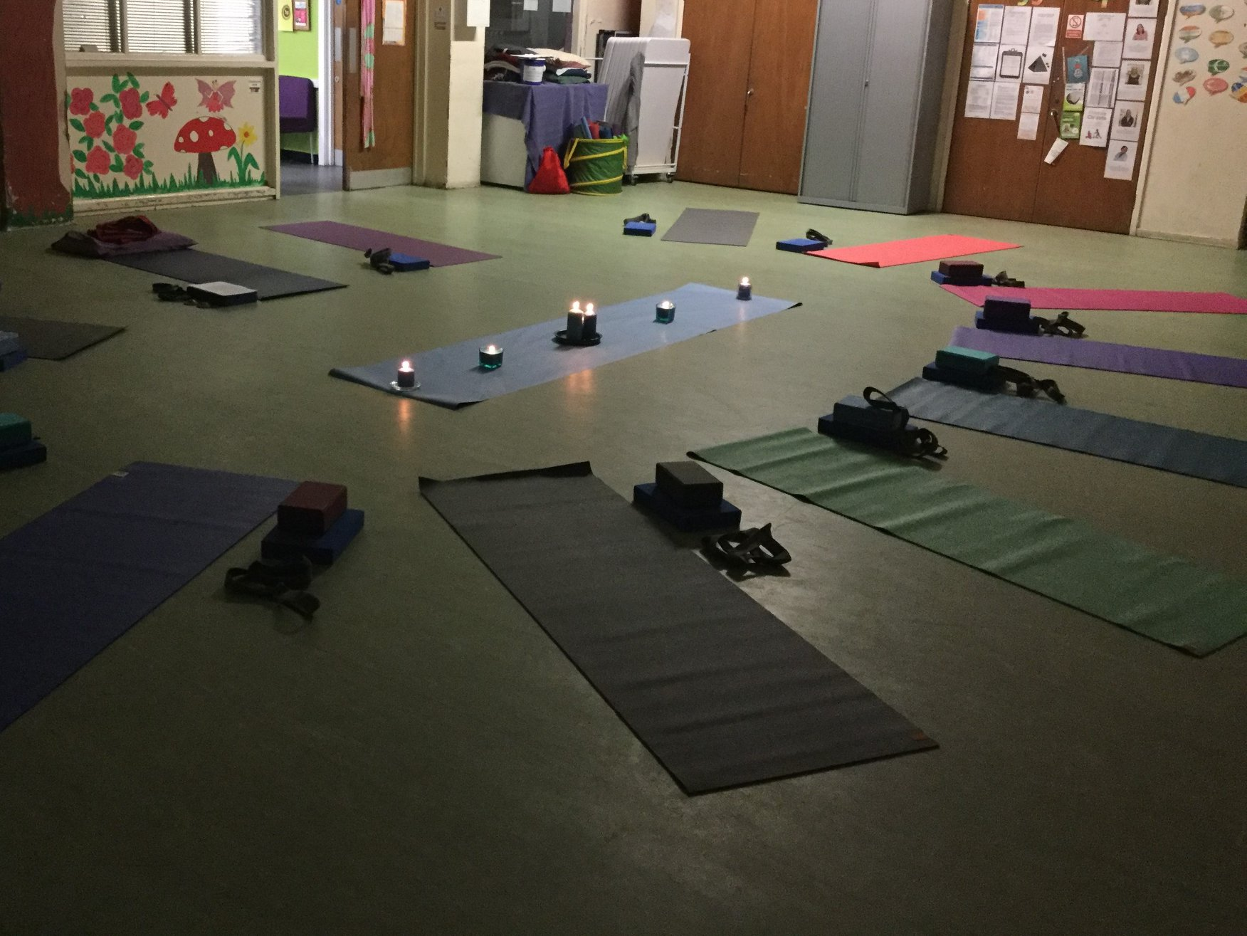 Setup of a Yoga for All Manchester session back in April 2019: yoga mats, candles, blocks in a dimly lighted room
