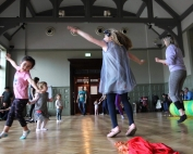 Image is a photograph of children dancing around the Grand Hall of the Whitworth Art Gallery