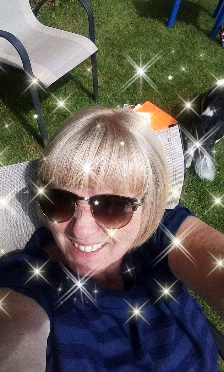 Image is a photograph of Karen, sat in a garden, looking up to the camera and smiling, with a twinkling star effect applied to the photograph