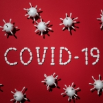 the word 'Covid-19' spelled out using medicine tablets, surrounded by virus figures | photo credit: Edward Jenner from Pexels.com