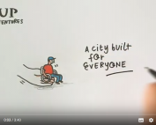 """A hand, a boy sitting on a wheelchair and the words """"A city built for everyone"""" 