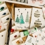 handcrafted Christmas cards and art materials on a table | image source: pexels.com