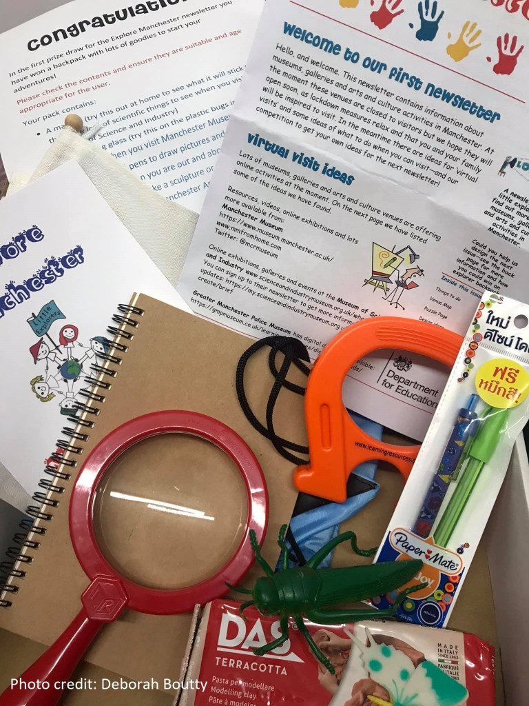 contents of the Explore Manchester package, which includes the newsletter, a notebook, pens, orange magnet, red magnifying glass, plastic grasshopper, modelling clay, and the Explore Manchester Passport