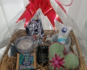 a plastic-wrapped hamper basket containing a candle, chocolate, mug, hand cream, heart-shaped pillow, jam, and soap, with a red ribbon on top