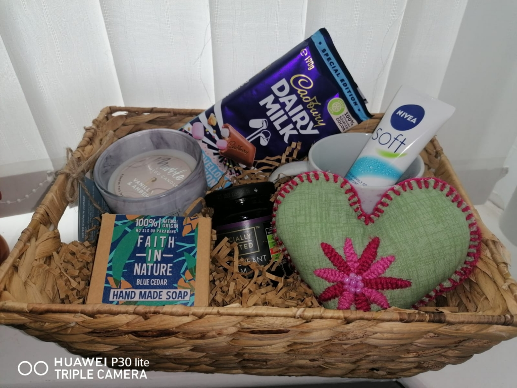 a hamper basket containing a candle, chocolate, mug, hand cream, heart-shaped pillow, jam, and soap