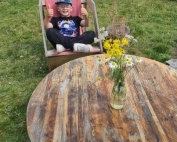 A happy boy is sitting on a lounger and showing two thumbs up, while at the Platt Fields Market Garden.