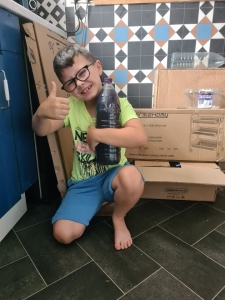 """A smiling boy gives a thumb up while holding his """"rocket fuel"""" bottle."""