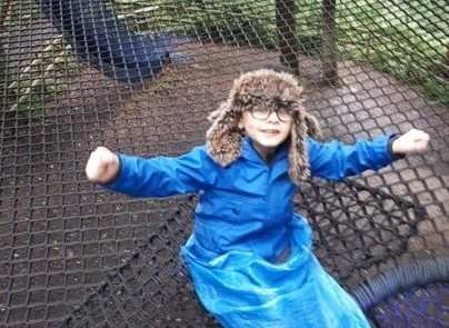 A boy is about to slide down the tunnel at Treetop Nets Heaton Park.