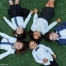 Five smiling children lying down on grass, looking up at the camera