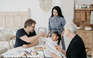 A man gives a fistbump to his daughter while the mum and a social worker looks on. In front of them is a table filled with paper and coloured pens, among other things.
